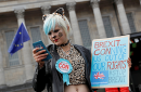 A protester looking at her phone during an anti-Brexit demonstration