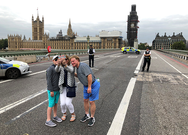 Tourists pose for a group selfie
