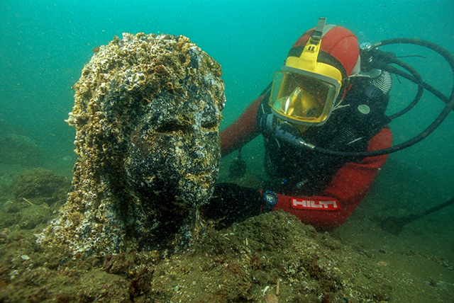 An archaeologist inspecting the still-encrusted head of a statue of a queen on site underwater in Thonis-Heracleion, Ptolemaic period (332-30 BC).