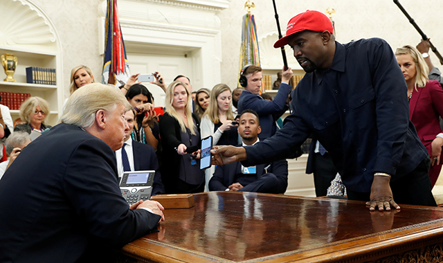 photo of kanye west showing phone to donald trump in oval office