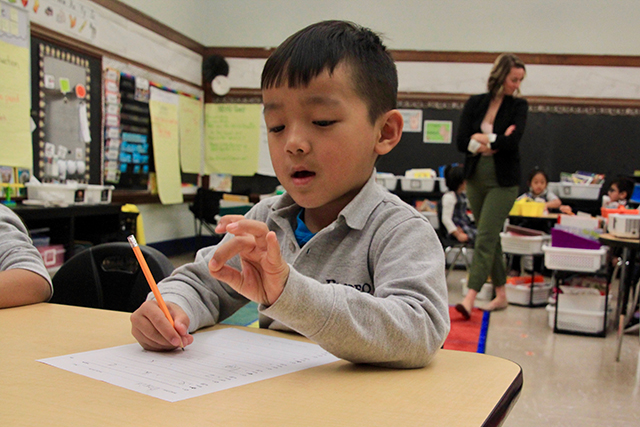 A first-grade student at Prodeo Acadmey's St. Paul campus tapping out a word he's been asked to write during a routine literacy assessment.
