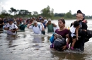 photo of central american migrants wading river
