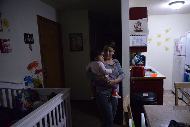 photo of woman holding toddler in apartment