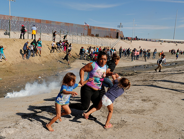 photo of migrants running from tear gas at border