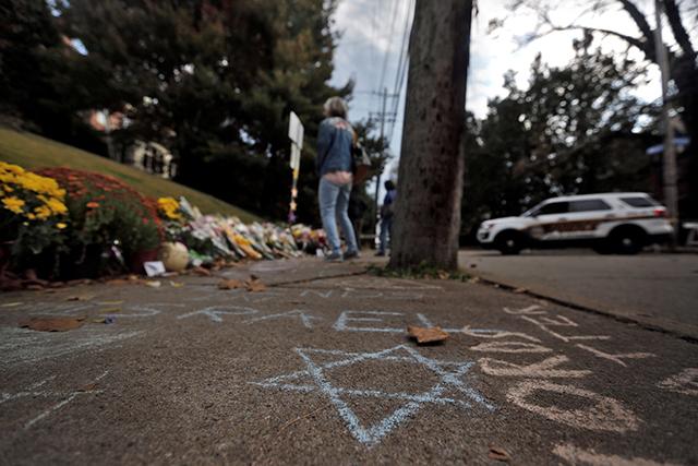 photo of woman praying at memorial for synagogue shooting victims