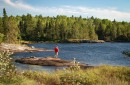 photo of man standing by lake in boundary waters