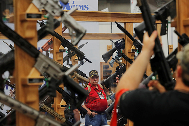 Gun enthusiasts looking at rifles during the annual National Rifle Association convention in Dallas, Texas.