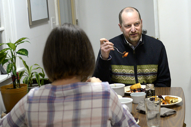 Dave Colling, right, eating dinner together with his wife, Sarah Steil, foreground.