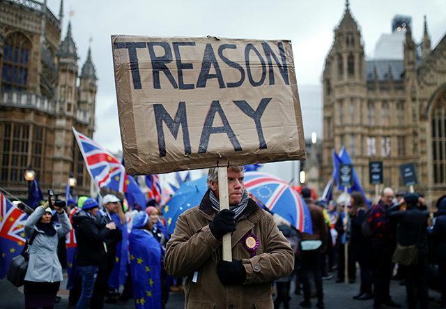 A pro-Brexit protester holding a banner as anti-Brexit protesters demonstrate outside the Houses of Parliament in London on January 15.