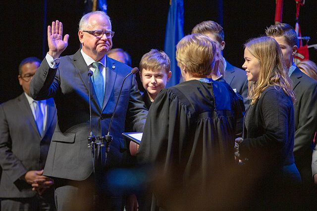 Gov. Tim Walz, surrounded by family, taking the oath of office Tuesday at the Fitzgerald Theater in St. Paul.
