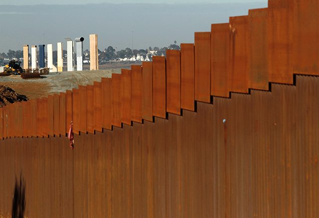 photo of fence at border with wall prototypes in background