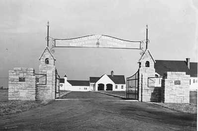 historical photo of gate in front of buildings