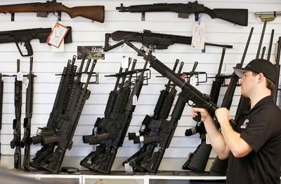 photo of man holding rifle inside gun shop