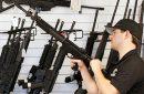 photo of a man holding a rifle in a gun shop
