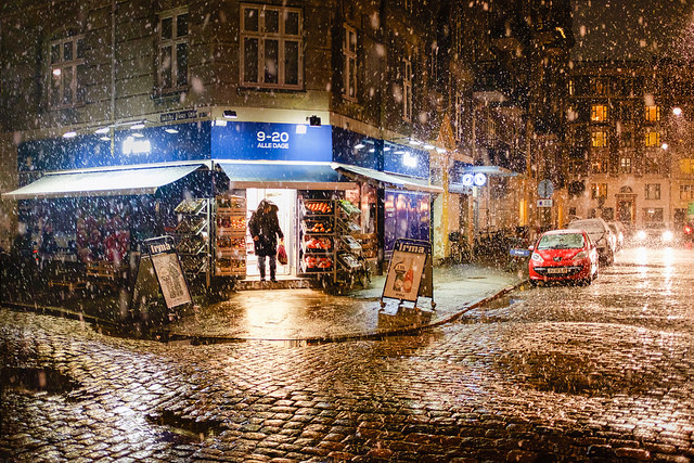 photo of person emerging from shop with snow falling in front