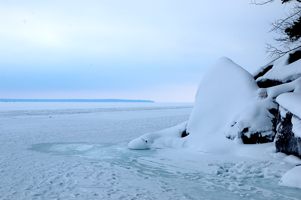 Lake Superior appears frozen between the mainland shore and Basswood Island.