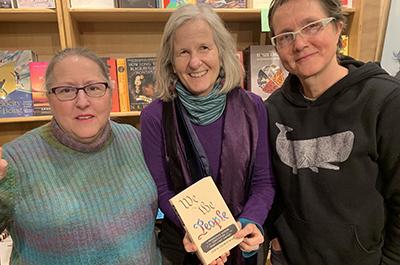 photo of three women holding abook