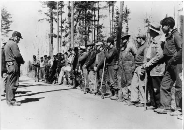 historical photo of workers lined up by a road