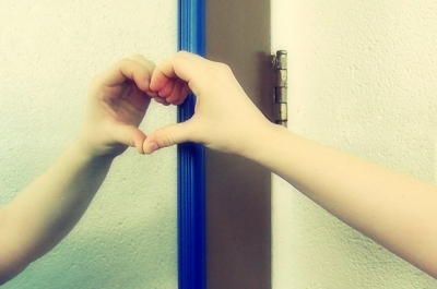 photo of hand held up to mirror to create heart shape