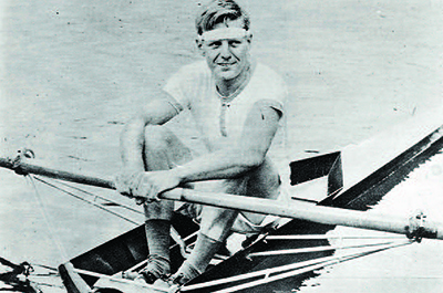 historical photo of man sitting in scull with oars in hand