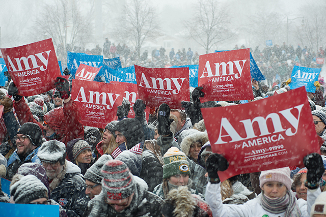 photo of people holding red and blue amy klobuchar signs at a rally