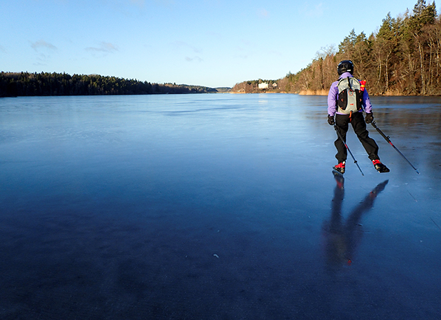 photo of woman skating across frozen lake