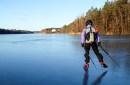 photo of woman skating across frozen lake