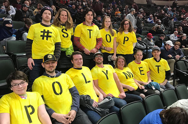 photo of protesters wearing t shirts that collectively spell stop polymet
