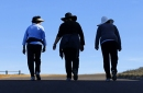 Women walk together up a hill