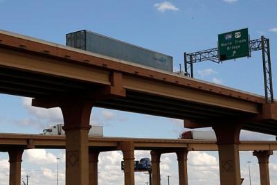 photo of semi truck driving over bridge
