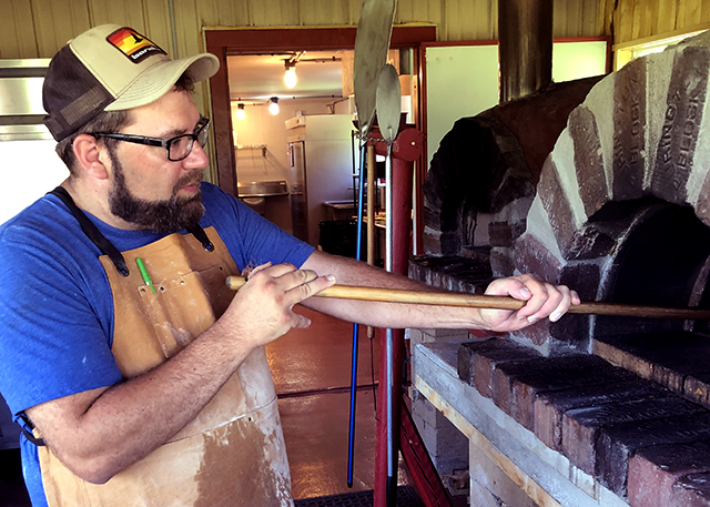 Bill Bartz checks a pizza in one of two wood-fired brick ovens.