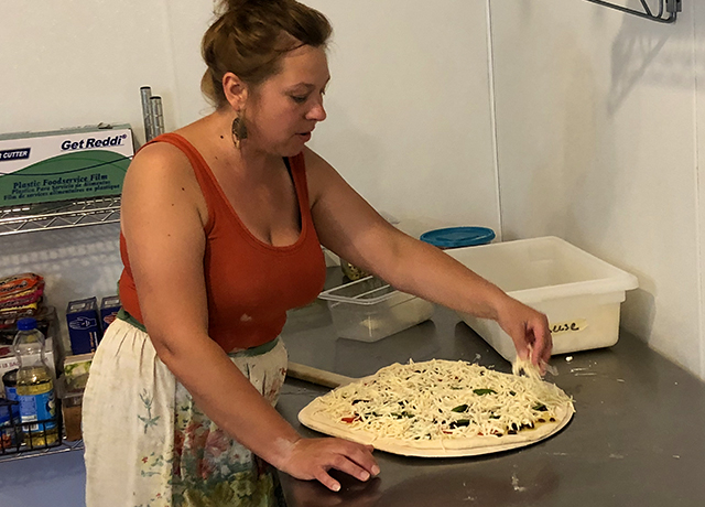 Emily Knudsen prepares a pizza in the kitchen, which is in a renovated horse barn.