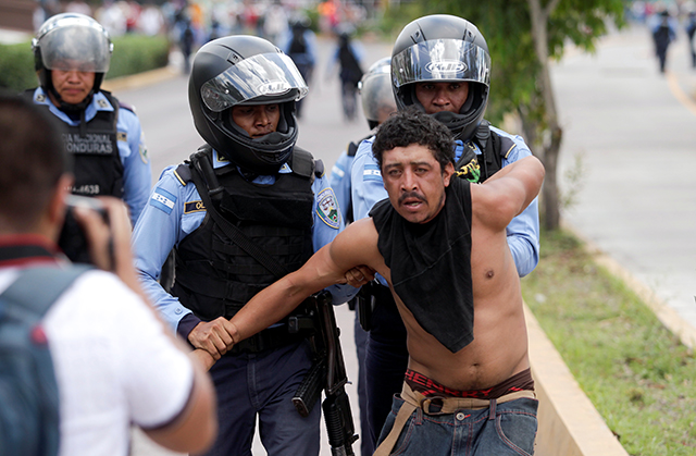 Policemen detain a demonstrator during a march