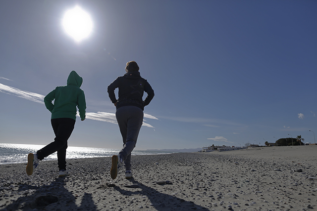 photo of two joggers on the beach