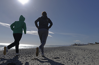 photo of two people jogging on beach