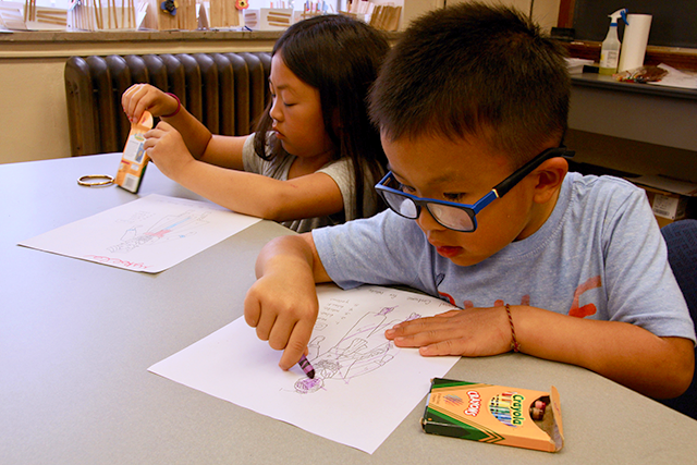 Camp participants coloring paper dolls adorned in traditional Hmong clothes.