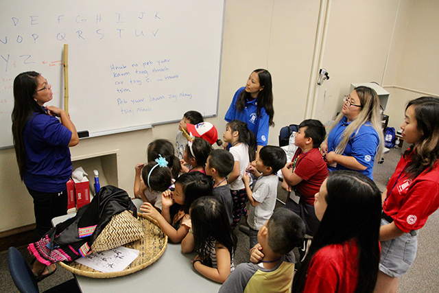 Chao Vang teaching the Hmong alphabet to a group of Kindergarteners.