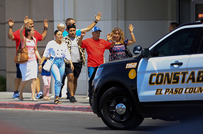 Shoppers exiting with their hands up after a mass shooting at a Walmart
