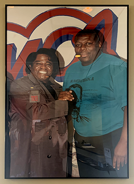 A poster of soul legend James Brown and KMOJ legend Q Bear greets visitors to the station's headquarters.