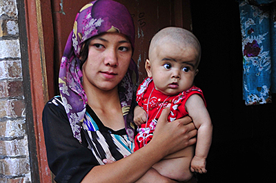 An ethnic Uyghur woman hugs her son