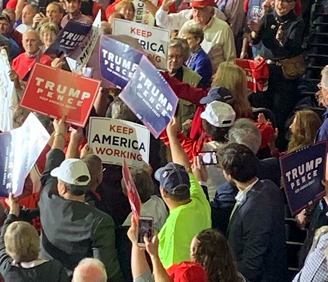 Trump fans covered a protester's sign, then booed him out of the section and into the hands of police and Target Center security, who escorted him from the building.