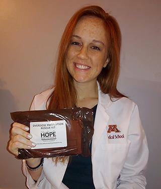 Ally Fuher holding a Naloxone kit.