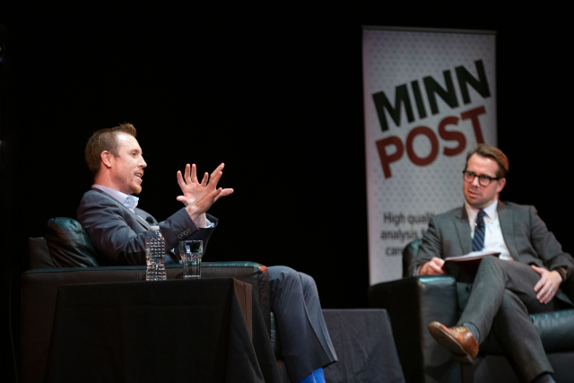 photo of two men talking on stage
