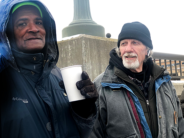 A man named Alex, left, takes help from Todd Feske, who helps people sleeping outside in St. Paul with supplies and company. Most nights, Alex sleeps on a bench that overlooks the Mississippi River.