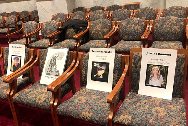 Members of advocacy groups set up posters with photos of people who have died at the hands of MPD on empty chairs in council chambers during Friday's meeting.