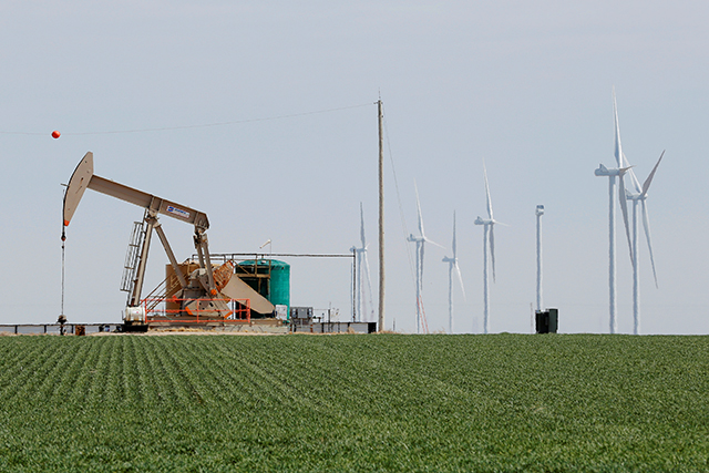 An oil derrick and wind turbines stand above the plains north of Amarillo, Texas.