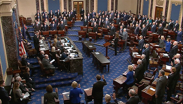 Chief Justice of the United States John Roberts swearing in senators during the procedural start of the Senate impeachment trial on Thursday.