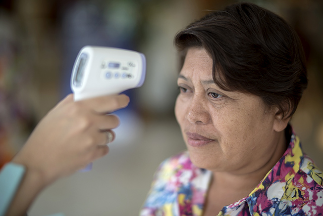 A woman gets her temperature checked