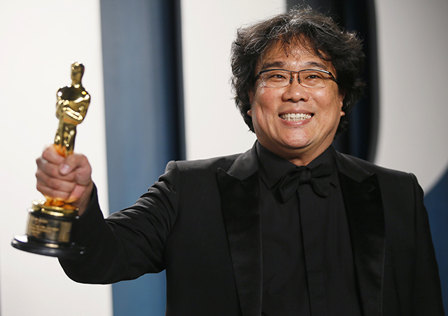 """Bong Joon Ho holding one of his Oscars for """"Parasite"""" at the Vanity Fair Oscar party in Beverly Hills on Sunday."""