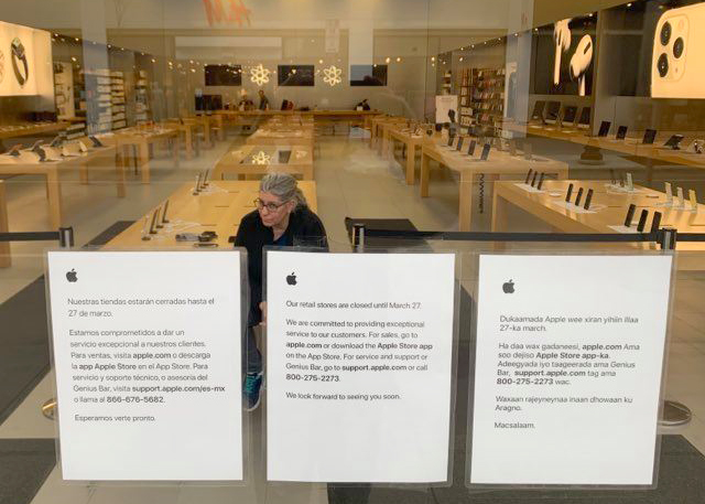 A forlorn employee sits and stares out of the shuttered front door of the Apple Store onto an empty Hennepin Avenue in Uptown Minneapolis on Monday, March 16.